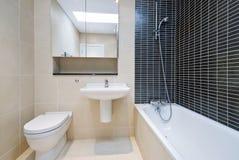 Cuarto de baño moderno de la en-habitación en amarillento con los azulejos negros fotografía de archivo