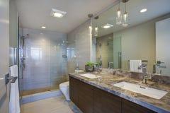 Cuarto de baño principal de gran altura moderno con el gabinete dual de la vanidad fotos de archivo