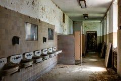 Cuarto de baño que desmenuza con los fregaderos - hospital abandonado Fotos de archivo