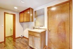 Cuarto de baño vacío con los gabinetes de madera Imágenes de archivo libres de regalías