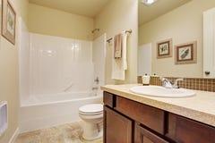 Cuarto de baño vacío en color de marfil suave con el ajuste de la pared de la teja Imagen de archivo