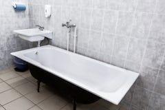Cuarto de baño viejo con el fregadero y las paredes tejadas URSS foto de archivo