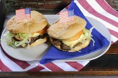 Cuarto de los E.E.U.U. de las hamburguesas de julio en bandeja de madera Fotos de archivo libres de regalías