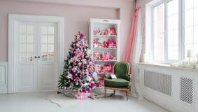 Cuartos adornados holdiay hermosos con los árboles de navidad, el estante y los regalos azules rosados en él, interior verde del  Fotos de archivo libres de regalías