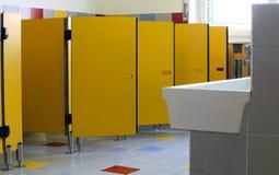 Cuartos de baño del cuarto de niños con las puertas amarillas de cabinas Imagenes de archivo