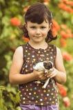 Cuatro años de la muchacha que juega con el perrito en el jardín Imagenes de archivo