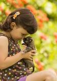Cuatro años de la muchacha que juega con el perrito en el jardín Fotografía de archivo