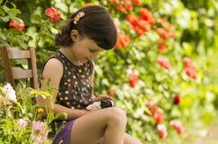 Cuatro años de la muchacha que juega con el perrito en el jardín Imagen de archivo libre de regalías