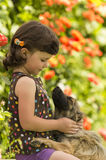 Cuatro años de la muchacha que juega con el perro en el jardín Imágenes de archivo libres de regalías