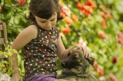 Cuatro años de la muchacha que juega con su perro en el jardín Fotografía de archivo