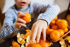 Cuatro años de muchacho comen un mandarín Fotografía de archivo
