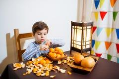 Cuatro años de muchacho comen un mandarín Imagen de archivo