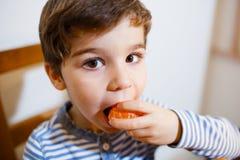 Cuatro años de muchacho comen un mandarín Imagenes de archivo