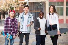 Cuatro adolescencias con los monopatines al aire libre Imagen de archivo