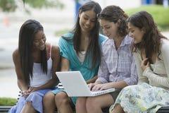 Cuatro adolescencias en una computadora portátil Fotos de archivo