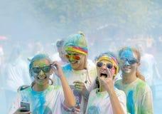 Cuatro adolescente y vidrios sonrientes cubiertos con color sacan el polvo Foto de archivo