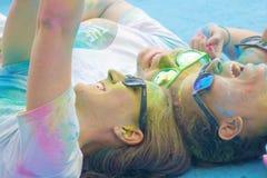 Cuatro adolescente y vidrios sonrientes cubiertos con color sacan el polvo de colocación Imagen de archivo libre de regalías