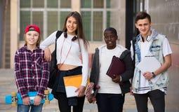 Cuatro adolescentes con las carpetas y las mochilas Imagen de archivo libre de regalías