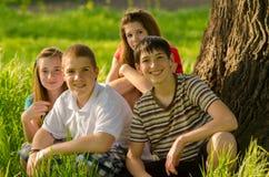 Cuatro adolescentes felices en la naturaleza Foto de archivo libre de regalías