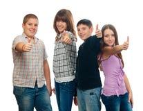 Cuatro adolescentes felices que muestran los pulgares para arriba Foto de archivo libre de regalías