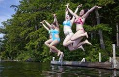 Cuatro adolescentes felices que saltan en el lago Imágenes de archivo libres de regalías