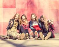 Cuatro adolescentes frescos con los patines Imagenes de archivo