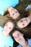 Cuatro adolescentes jovenes que miran para arriba la cámara Fotos de archivo