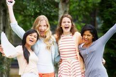 Cuatro adolescentes que celebran resultados acertados del examen Imagen de archivo libre de regalías