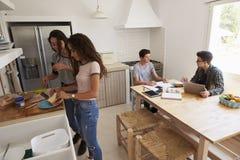 Cuatro adolescentes que hacen el almuerzo y que estudian junto en cocina Foto de archivo