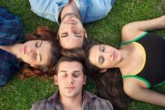 Cuatro adolescentes que se relajan en la hierba Foto de archivo libre de regalías