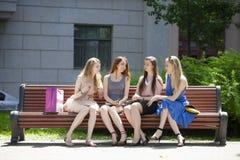 Cuatro adolescentes que se sientan en banco en parque del verano Imagen de archivo