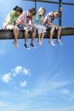 Cuatro adolescentes que se sientan en el puente de madera contra el cielo azul Foto de archivo libre de regalías