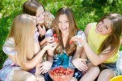 Cuatro adolescentes y fresas sonrientes bastante felices Imagen de archivo