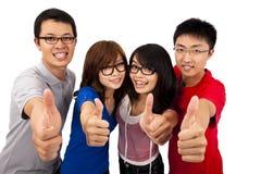 Cuatro adolescentes y pulgares jovenes para arriba Fotos de archivo libres de regalías