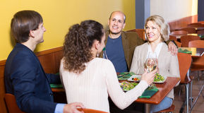 Cuatro adultos con el vino y la cena que ríen en restaurante Imagenes de archivo