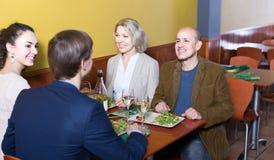 Cuatro adultos con el vino y la cena que ríen en restaurante Fotografía de archivo