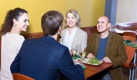 Cuatro adultos con el vino y la cena que ríen en restaurante Imagen de archivo