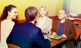 Cuatro adultos con el vino y la cena que ríen en restaurante Foto de archivo