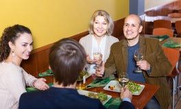 Cuatro adultos con el vino y la cena que ríen en restaurante Imagen de archivo libre de regalías
