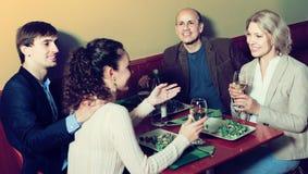 Cuatro adultos con el vino y la cena que ríen en restaurante Foto de archivo libre de regalías