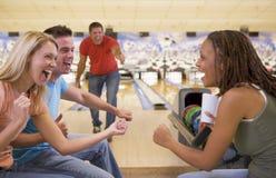 Cuatro adultos jovenes que animan en un callejón de bowling Fotografía de archivo libre de regalías