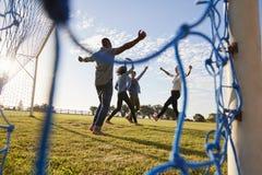 Cuatro adultos jovenes que animan una meta anotada en el partido de fútbol Fotografía de archivo