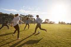Cuatro adultos jovenes que juegan a fútbol en un parque en la puesta del sol Fotografía de archivo