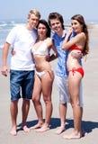 Cuatro adultos jovenes que se colocan en la playa en desgaste de la nadada Foto de archivo libre de regalías