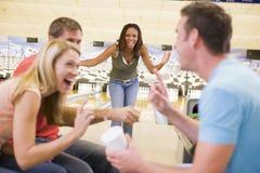 Cuatro adultos jovenes que se ríen de un callejón de bowling Imagenes de archivo