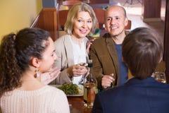 Cuatro adultos positivos felices con el vino y la cena que ríen en resto Foto de archivo
