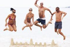 Cuatro adultos que saltan en la playa sobre castillo de la arena Foto de archivo libre de regalías
