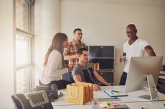 Cuatro adultos que se sientan alrededor del escritorio en el trabajo Fotografía de archivo