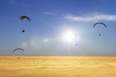 Cuatro alas flexibles sobre un mar de nubes con el sol Fotografía de archivo