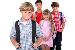 Cuatro alumnos con las mochilas Imágenes de archivo libres de regalías